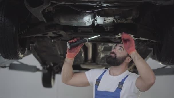 Úspěšné vousatý mechanik kontrola odpružení nebo brzd v autě s baterkou zdvižené automobilu v servisním centru. Obratný muž v uniformě, oprava aut