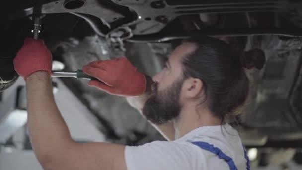 Vousatý auto mechanik šroubování podrobnosti o auta se speciálním nástrojem na zdvižené automobil v servisním centru zblízka. Obratný muž v uniformě, oprava aut