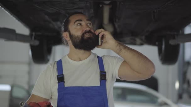 Vousatý automechanik kontrola odpružení nebo brzd v autě zdvižené automobilu v servisním centru zblízka. Obratný muž mluví o mobilní telefon, pak vezme Foto spodní části vozu