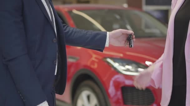 Unrecognizable man in suit drops keys in the hand of a woman, but they fall to the floor close up. Red automobile in the background. Concept of buying a vehicle, auto business