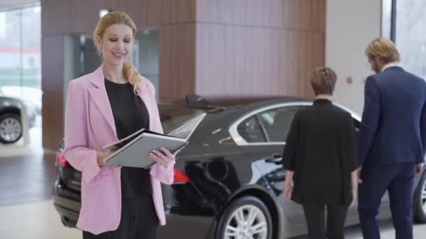 Portrét příjemná žena v růžové sako ve velké knize s informacemi o autech před pár výběru vozidla. Koncepce na nákup automobilu, automobilový průmysl