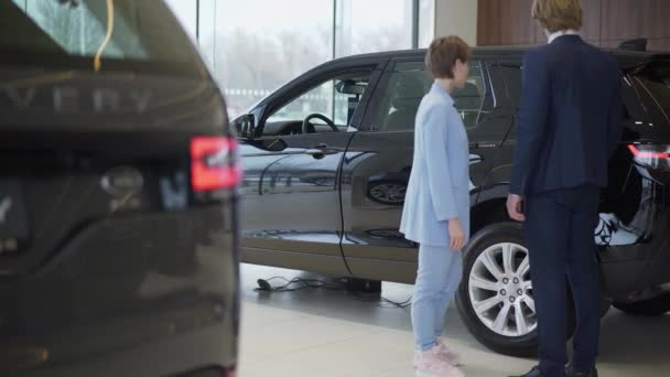 Successful stylish business couple chooses a new car in a luxury motor show. Car showroom