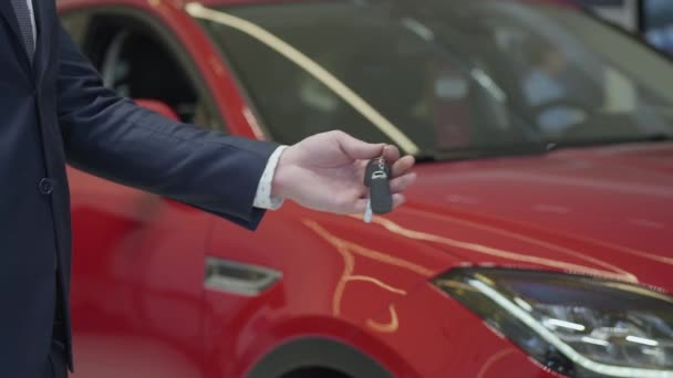 Unrecognized salesman gives a car keys to unrecognized businesswoman and shake hands in the car dealership. Car showroom