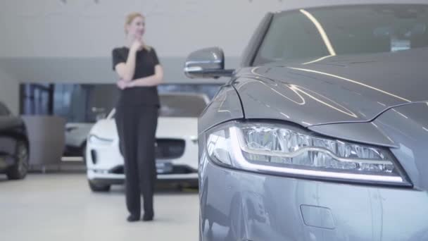 Blurred woman figure in black wear standing in motor show looking around. Headlight of modern silver car in the foreground. Customer choosing automobile to buy. Concept of buying vehicle. Car showroom