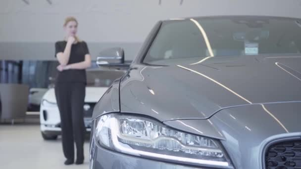 Customer choosing automobile to buy. Blurred woman figure in black wear standing in motor show looking around. Headlight of modern silver car in the foreground. Concept of buying vehicle. Car showroom