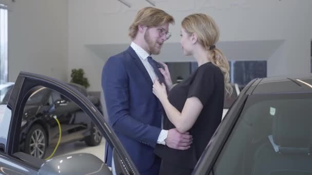 Happy man and woman just bought car in modern motor show. Couple hugging near automobile with opened door in a car dealership. Businessman buying vehicle for wife