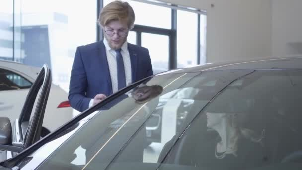 Handsome young car salesman discussing new automobile model in motor show. Car dealership.