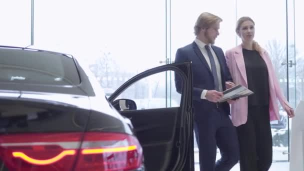 Jouful couple chooses a new vehicle in a car dealership. Car showroom.
