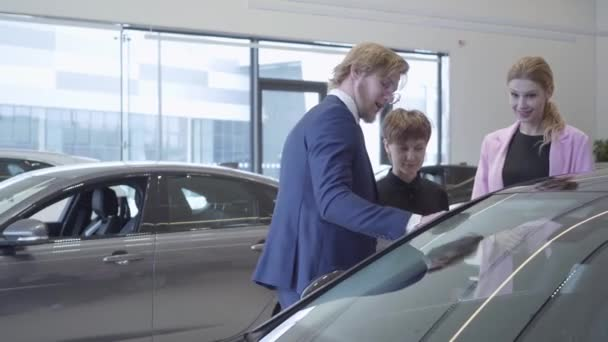 Confident salesman in suit and two female clients talking near modern car. Women choosing vehicle consulting with professional seller. Concept of buying automobile