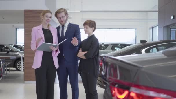 Car saleswoman shows a young couple information about luxury car in expensive car showroom. Successful couple buys a new auto at a prestigious car dealership.