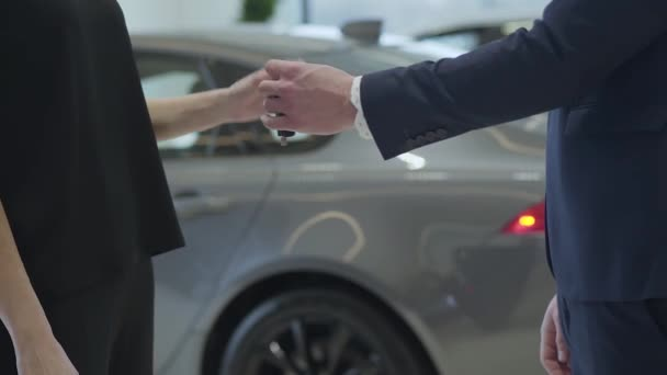 Unrecognized confident professional salesman in a business suit gives a car keys to unrecognized businesswoman and shake hands in the car dealership. Girl shakes the keys showing off. Car showroom