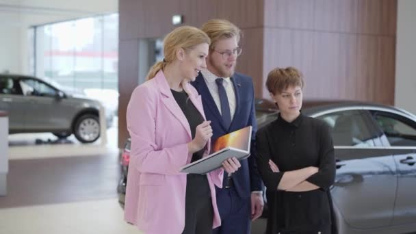 Salesswoman in pink jacket showing information in book to customers. Professional saleswoman helps man and woman to choose vehicle. Concept of buying automobile, auto business