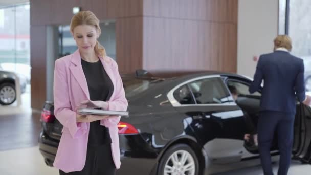 Portrait of pleasant cute girl in pink jacket with a big book about cars in front of couple choosing vehicle. Man opens the door and woman sits inside. Concept of buying automobile, auto business