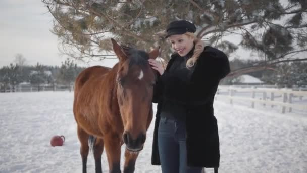 Young blond woman petting face and mane of beautiful brown horse at a ranch. Lady takes off hat and puts on the horses head. Girl in warm clothing spends time with horses in the winter paddock
