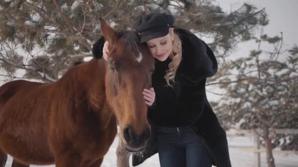 Mladá blond žena mazlit tvář krásné hnědé koně na ranči. Lady, objímání a líbání zvíře. Dívka v teplé oblečení tráví čas s koněm v zimním výběhu