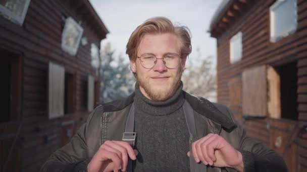 Portrait of a handsome bearded guy with glasses dressed in a warm sweater and wide-open jacket. Guy smiles, pulls up suspenders and looks around. Slow motion.