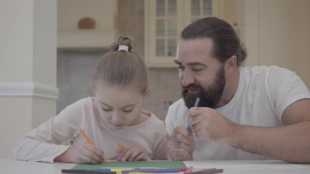 Bearded man looking at his little girl drawing with markers while sitting at the table at home. Father advising his daughter how to draw. Small girl spends time with daddy sitting in the kitchen