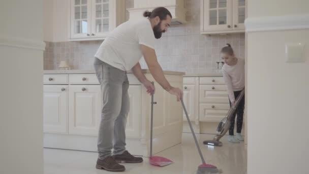 Táta s vousy a malá roztomilá dcera sweep a vakuum v nové moderní kuchyni s smeták a lopatku
