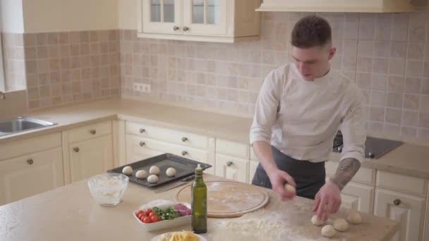 Fiatal pizza maker cook egységes elhelyezés tésztát golyó pizza sütés tálca a konyhában. Élelmiszer-készítmény fogalmát. Felülnézet, forgatás felülről