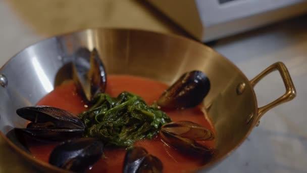 Fischfilet in einer tiefen Aluminiumpfanne mit Henkeln mit roter Sauce darin und Muscheln, die mit Gewürzen bestreut sind, Salz und Pfeffer aus nächster Nähe. Gourmet-Kochkonzept.