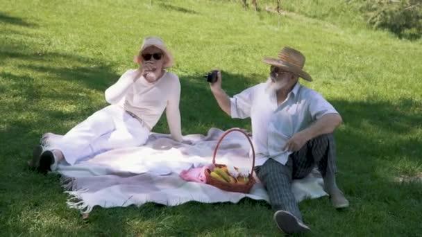 Reifer Mann mit Hut fotografiert seine elegante Frau beim Picknick mit einem Glas Wein