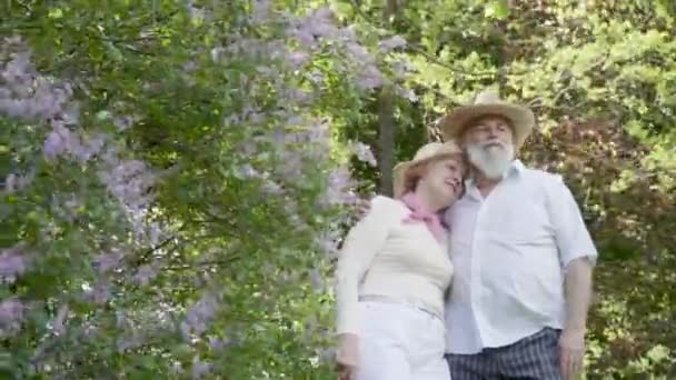Senior man and senior woman enjoy each other in summer park