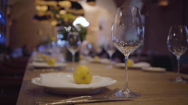 Serving a table in an expensive restaurant. Empty wine glasses, white plates, cutlery on a wooden table. Juicy lemons lie on the plates.