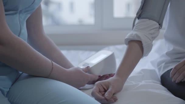 Közelről női medicine doktor vérnyomásmérés fiatal nő. Egészségügyi ellátás, egészséges életmód és orvosi szolgáltatás. Kamera mozog balra