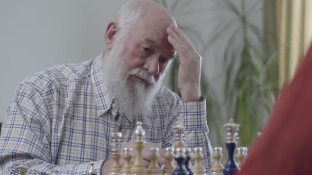 Régi barátok ül otthon a bőr kanapé sakk játék. Szakállas ember arra gondolt, milyen sakk darab, hogy a lépés. Kaukázusi vénnek szomszédok játék sakk-vidáman, beltéri