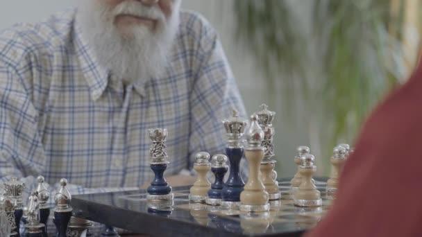 Die Hand eines unkenntlichen Mannes legt eine Schachfigur hin. zwei Männer beim Händeschütteln über einem Schachbrett. das schöne Schachset mit silbernen Einsätzen, die auf dem Schachbrett stehen, aus nächster Nähe. Geschäftskonzept