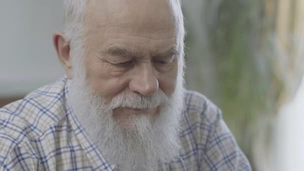 Portrait of thoughtful bearded mature man sitting at home close up. Senior man feels uncomfortable. Old man has a problem