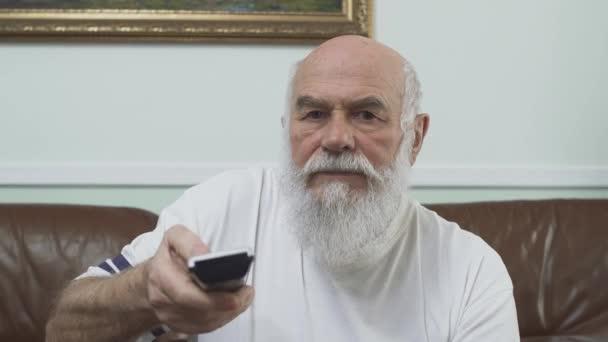 Portré érett idősebb ember ül a barna bőr kanapé, néz Tv. öreg kapcsolók csatornák segítségével a távoli fehér póló. Szabadidő a nyugdíjas