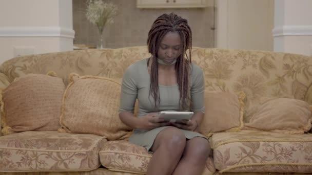 schöne afrikanisch-amerikanische Frau sitzt im Wohnzimmer auf dem Bus und sucht etwas auf dem Tablet