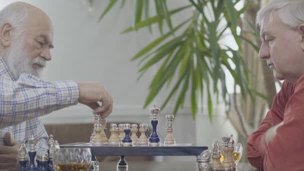 Két érett vezető barátai sakkozás közben ül otthon. Kaukázusi öregember szomszédok sakkozás örömteljesen beltérben. Hírszerzési kihívás koncepció