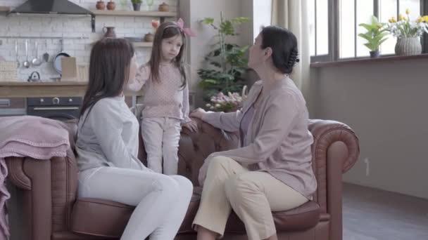 Großmutter, Mutter und kleine Tochter sitzen zusammen auf dem Sofa in einer modernen Wohnung. das Mädchen steht auf der Kiste, Mutter und Oma schauen sie lächelnd an. Konzept der Erzeugung.