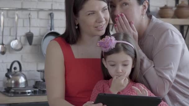 Großmutter, Mutter und kleine Tochter sind zusammen in einer modernen Wohnung. das Mädchen mit dem Spielzeug, die Oma flüstert der Mutter ins Ohr. Konzept von Generationen, Liebe, Familie