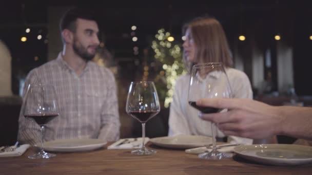 Rozmazané postavy vousatý muž a elegantní žena mluvila v pozadí sedí v moderní komfortní restauraci u stolu. Ruka člověka bere sklenka na červené víno a dát ji zpět na stůl