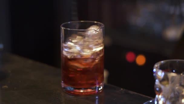 Barkeeper macht Cocktail in der Bar aus nächster Nähe. Barmann Hand Alkohol mit Eiswürfeln im Glas mischen. Nachtleben, ungesunder Lebensstil