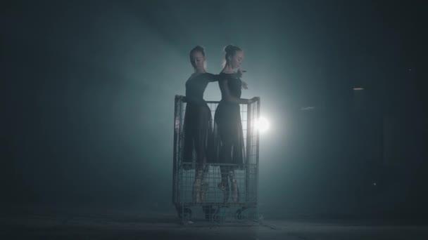 Zwei grazile professionelle Balletttänzerinnen tanzen auf ihren spitzen Ballettschuhen im Scheinwerferlicht auf schwarzem Hintergrund im Studio. Ballerinas zeigen klassischen Ballett-Pas im Metallwagen.