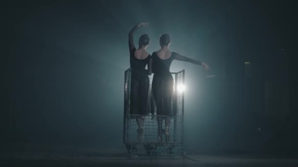 Two graceful diligent ballerinas dancing on her pointe ballet shoeses in spotlight on black background in studio. Ballet dancers shows classic ballet pas standing in a metal trolley.