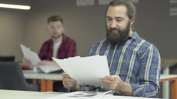 Colleagues read papers with work plans. One office worker or businessman is indignant at bad pokachateley and shouts at his colleague. Two bearded office workers work in the office studying the