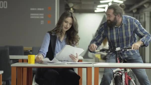 Joyful colleagues chatting in the workplace. Successful office workers share the news. Bearded man on a bicycle and beautiful business woman with papers.