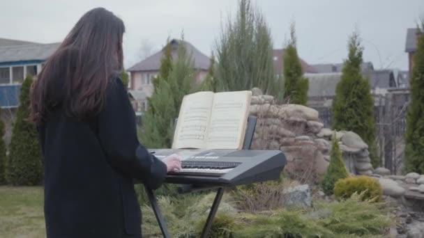Hivatásos zongorista játszik klasszikus zongorajáték a szintetizátor a kertben. Valódi emberek sorozata.