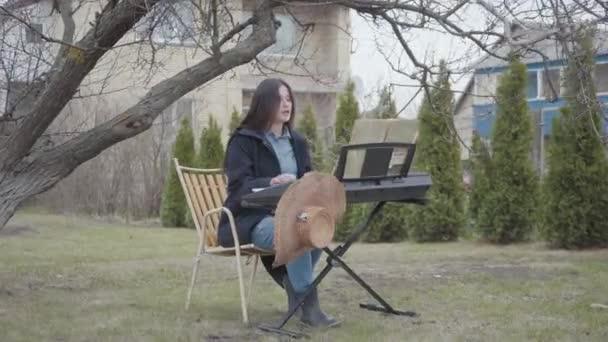 Tehetséges gyönyörű barna lány szenvedélyes játék szintetizátor és énekel ülve a fa alatt a kertben a szabadban. Romantika, meditáció, elektronikus zene