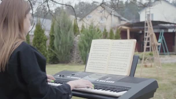 Professzionális aranyos zongorista játék klasszikus zongora zene a szintetizátor a kertben. Valódi emberek sorozata.