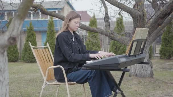 Professzionális aranyos női zongorista játszik klasszikus zongoramuzsika a szintetizátor a kertben. Valódi emberek sorozata.