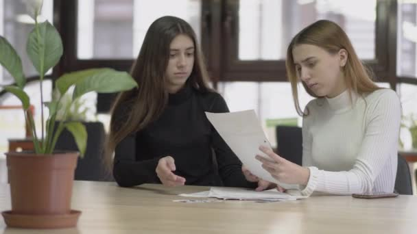 Two colleagues discuss business papers with reports or plans for the future sitting at a table in a modern business office. Concept of business workplace.