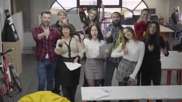 Velký přátelský kancelářskej tým se usmívá a zobrazuje velké prsty v kameře a stojí ve velké kancelářské místnosti.