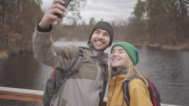 Young couple of travelers taking selfie while standing on a bridge against the background of a small river. Young people are dressed in jackets and hats. Vacation successful independent young people.