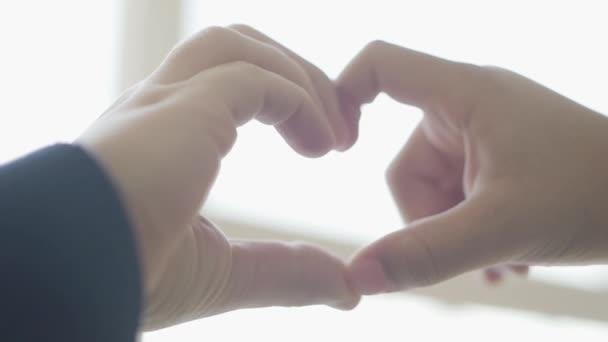 Aranyos gyerekek ábrázolnak szív alakú ujjaikkal közelről. Szív alakú gyermek kezek. A szeretet, a barátság, a béke fogalma
